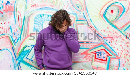 young bearded crazy man feeling sad, frustrated, nervous and depressed, covering face with both hands, crying against graffiti wall stock photo