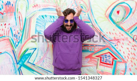young bearded crazy man feeling stressed and anxious, depressed and frustrated with a headache, raising both hands to head against graffiti wall stock photo