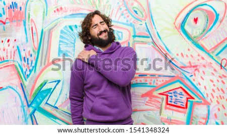 young bearded crazy man feeling tired, stressed, anxious, frustrated and depressed, suffering with back or neck pain against graffiti wall stock photo