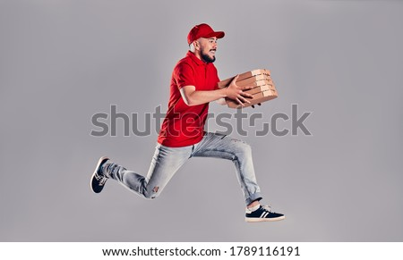 Young bearded delivery man in a red uniform runs in a jump flight holds boxes with pizza isolated on gray background. Fast home delivery of pizza.