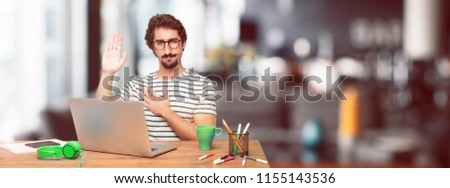 young bearded graphic designer with a laptop smiling confidently while making a sincere promise or oath, solemnly swearing with one hand over heart.