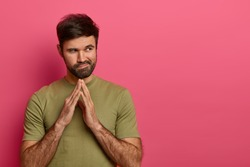 Young bearded guy steepls fingers and looks aside, has good plans and intention to do something, wears t shirt, has mysterious thoghtful expression, isolated on pink background, free space aside