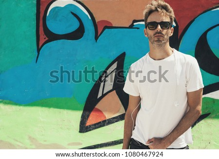 Young bearded handsome man standing next to a colorful wall background wearing an empty white t-shirt and sunglasses. Horizontal mock up style.