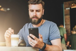 Young bearded hipster man sits at table in cafe and uses smartphone.On table cup of coffee.Guy is chatting,working,blogging,learning online. Social media, marketing. Online education.Instagram filter.