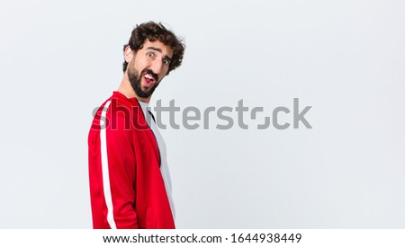 young bearded man back view feeling puzzled and confused, with a dumb, stunned expression looking at something unexpected against copy space wall