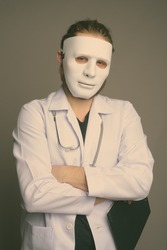 Young bearded man doctor wearing a mask against gray background