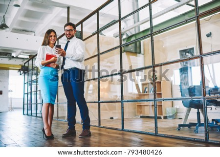 Young bearded man in eyeglasses communicating with smiling attractive female colleague and showing interesting video in website on smartphone.Positive employees reading news on webpage in office