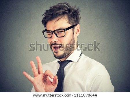 Young bearded man in glasses showing OK gesture and blinking at camera with overconfidence