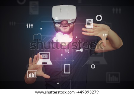 Photo of Young bearded man in VR-headset is surrounded by virtual data on interactive touch screen over dark background
