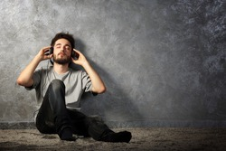 Young bearded man listening music with headphones on grey wall background