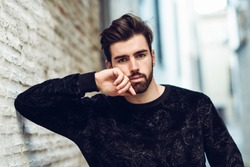 Young bearded man, model of fashion, looking at camera in urban background wearing casual clothes. Guy with beard and modern hairstyle in the street.