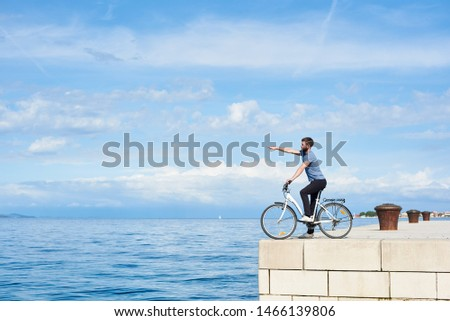 Young bearded man on bicycle on high paved stone sidewalk pointing at distant mountain on opposite shore on clear blue sea water and small sailing boat background. Active holiday and tourism concept. #1466139806
