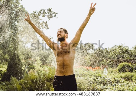 Young bearded man outside in green summer nature holding garden hose spraying himself, lifted high in the air and bright sun lighting him through leaves of a tree, toned retro effect.sunny rain