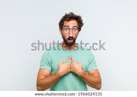 young bearded man pointing to self with a confused and quizzical look, shocked and surprised to be chosen Stock photo ©