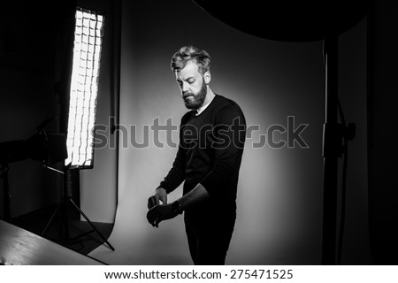 Young bearded man posing against black background at photo studio. Black and white photography.