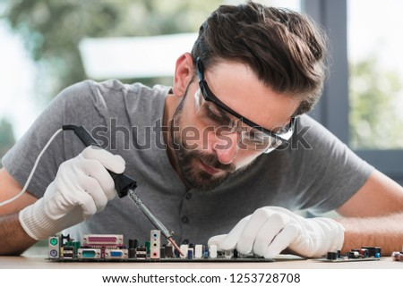Young Bearded Man Repairing Motherboard from PC. Repair Shop. Worker with Tools. Computer Hardware. Magnifying Glass. Soldering Iron. Digital Device. Laptop on Desk. Electronic Devices Concept. #1253728708