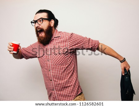 Young bearded man running wearing glasses, is late to work, coffee to go. Young man scared to be late, in a hurry or rush. Rush hour concept.