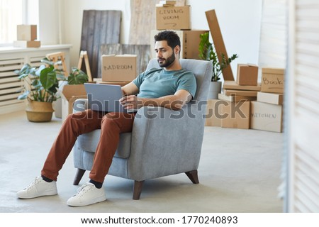 Young bearded man sitting on armchair and using laptop computer he moving to new apartment