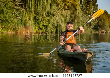 Young bearded man sitting with paddle in kayak in the middle of the lake #1198146727