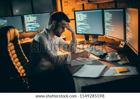 Young bearded man trader at office sitting at table covering face tired waiting for data upload