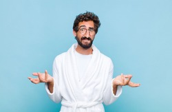 young bearded man wearing a bath robe feeling clueless and confused, not sure which choice or option to pick, wondering