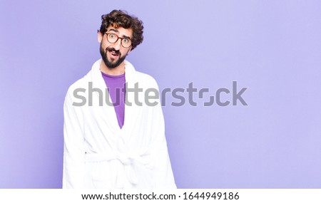 young bearded man wearing bathrobe feeling puzzled and confused, with a dumb, stunned expression looking at something unexpected