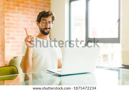 young bearded man with a laptop feeling like a genius holding finger proudly up in the air after realizing a great idea, saying eureka Сток-фото ©