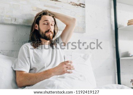 young bearded man with long hair having hangover and taking pill with glass of water in bedroom at home