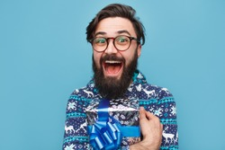 Young bearded man with wrapped blue gift isolated on blue background. Excited happy male with beard wearing winter sweater and holding christmas present box.