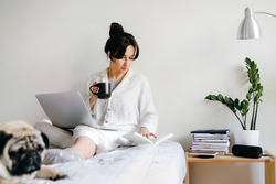 Young beatiful girl is reading a book and drinks tea on bed near a dog at home in isolation. Home office. Concept of working and studying in isolation.