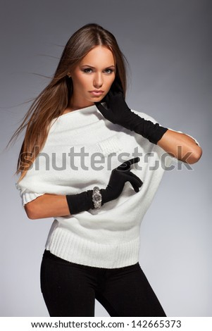 Young beautiful adult girl wearing elegant warm winter clothing. Studio shot
