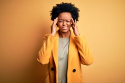 Young beautiful African American afro businesswoman with curly hair wearing yellow jacket with hand on head for pain in head because stress. Suffering migraine.