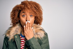 Young beautiful African American afro woman with curly hair wearing casual winter coat cover mouth with hand shocked with shame for mistake, expression of fear, scared in silence, secret concept