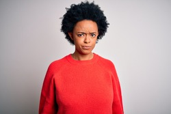 Young beautiful African American afro woman with curly hair wearing red casual sweater skeptic and nervous, frowning upset because of problem. Negative person.