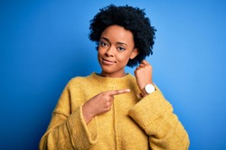Young beautiful African American afro woman with curly hair wearing yellow casual sweater In hurry pointing to watch time, impatience, looking at the camera with relaxed expression