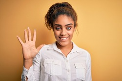 Young beautiful african american girl wearing casual shirt standing over yellow background showing and pointing up with fingers number five while smiling confident and happy.