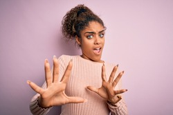 Young beautiful african american girl wearing casual sweater standing over pink background afraid and terrified with fear expression stop gesture with hands, shouting in shock. Panic concept.