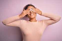 Young beautiful african american girl wearing casual sweater standing over pink background covering eyes with hands smiling cheerful and funny. Blind concept.