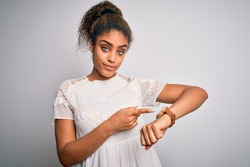 Young beautiful african american girl wearing casual t-shirt standing over white background In hurry pointing to watch time, impatience, upset and angry for deadline delay