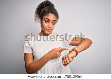 Young beautiful african american girl wearing casual t-shirt standing over white background In hurry pointing to watch time, impatience, upset and angry for deadline delay Stockfoto ©