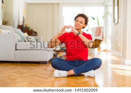 Young beautiful african american woman sitting on the floor at home smiling in love showing heart symbol and shape with hands. Romantic concept.