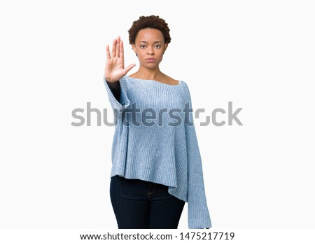 Young beautiful african american woman wearing a sweater over isolated background doing stop sing with palm of the hand. Warning expression with negative and serious gesture on the face.