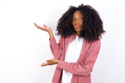 young beautiful African American woman wearing pink jacket against white wall pointing aside with both hands showing something strange and saying: I don't know what is this. Advertisement concept.