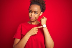 Young beautiful african american woman with afro hair over isolated red background In hurry pointing to watch time, impatience, looking at the camera with relaxed expression
