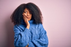 Young beautiful african american woman with afro hair wearing winter sweater over pink background thinking looking tired and bored with depression problems with crossed arms.
