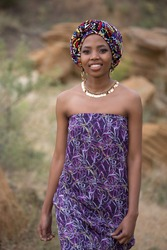 Young beautiful african girl in national clothes and jewelry on a background of yellow rocks