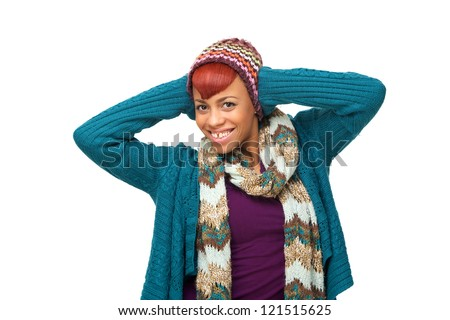 Young beautiful African girl in sweater, scarf and hat is isolated on white horizontal background. She is smiling looking at camera and has a fun expression on her face.