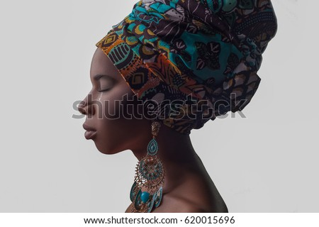Young beautiful African woman in traditional style with scarf, earrings crying, isolated on gray background. racism, depression or loneliness concept.