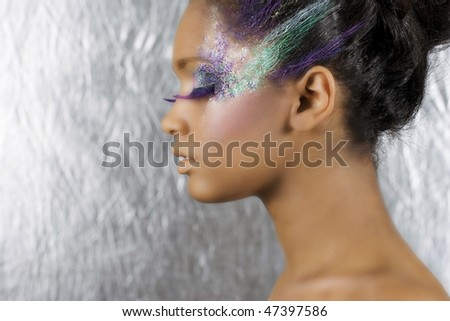 Young beautiful African woman with art make-up on a silver background