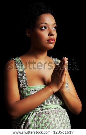 Young beautiful afro american pregnant woman praying against black background